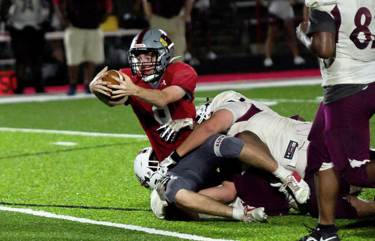 Redbirds quarterback Graham McAfoos (9) stretches for an extra yard late in the fourth quarter in Alton's 6-3 victory over Belleville West Friday night.