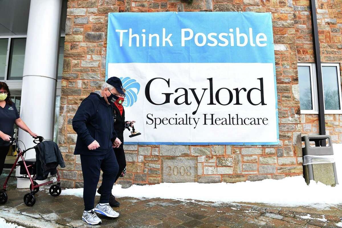 George Aiello of Bethel with the assistance of his wife, Kathleen, leaves Gaylord Specialty Healthcare in Wallingford after nearly nine months in hospitals recovering from COVID-19 on Dec. 18, 2020. At left is patient care technician Charlene Lewis.
