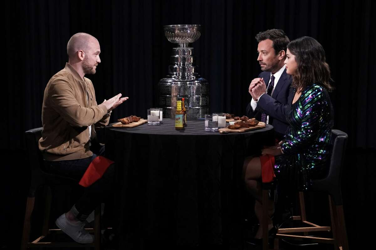 """""""Hot Ones"""" host Sean Evans samples wings with Jimmy Fallonand singer Selena Gomez during """"Hot Ones"""" on June 11, 2019 (Photo by: Andrew Lipovsky/NBCU Photo Bank/NBCUniversal via Getty Images via Getty Images)"""