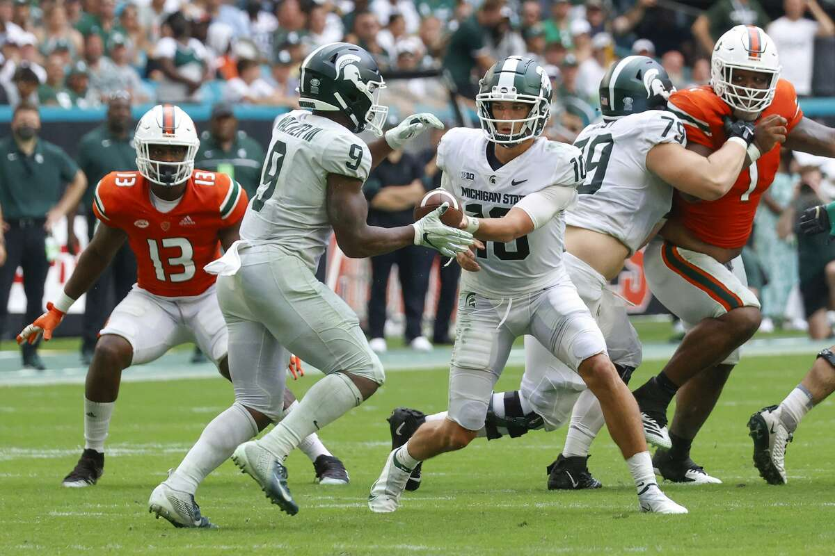 MIAMI GARDENS, FL - SEPTEMBER 18: Payton Thorne #10 hands the ball off to Kenneth Walker III #9 of the Michigan State Spartans against the Miami Hurricanes on September 18, 2021 at Hard Rock Stadium in Miami Gardens, Florida. . (Photo by Joel Auerbach/Getty Images)