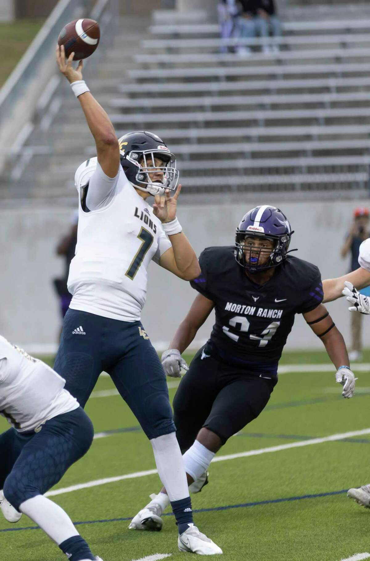 Lake Creek quarterback Cade Tessier (7) throws while under pressure from Morton Ranch defensive lineman Benen Lee (24) during the first quarter of a a non-district football game at Legacy Stadium, Thursday, Sept. 16, 2021, in Katy.