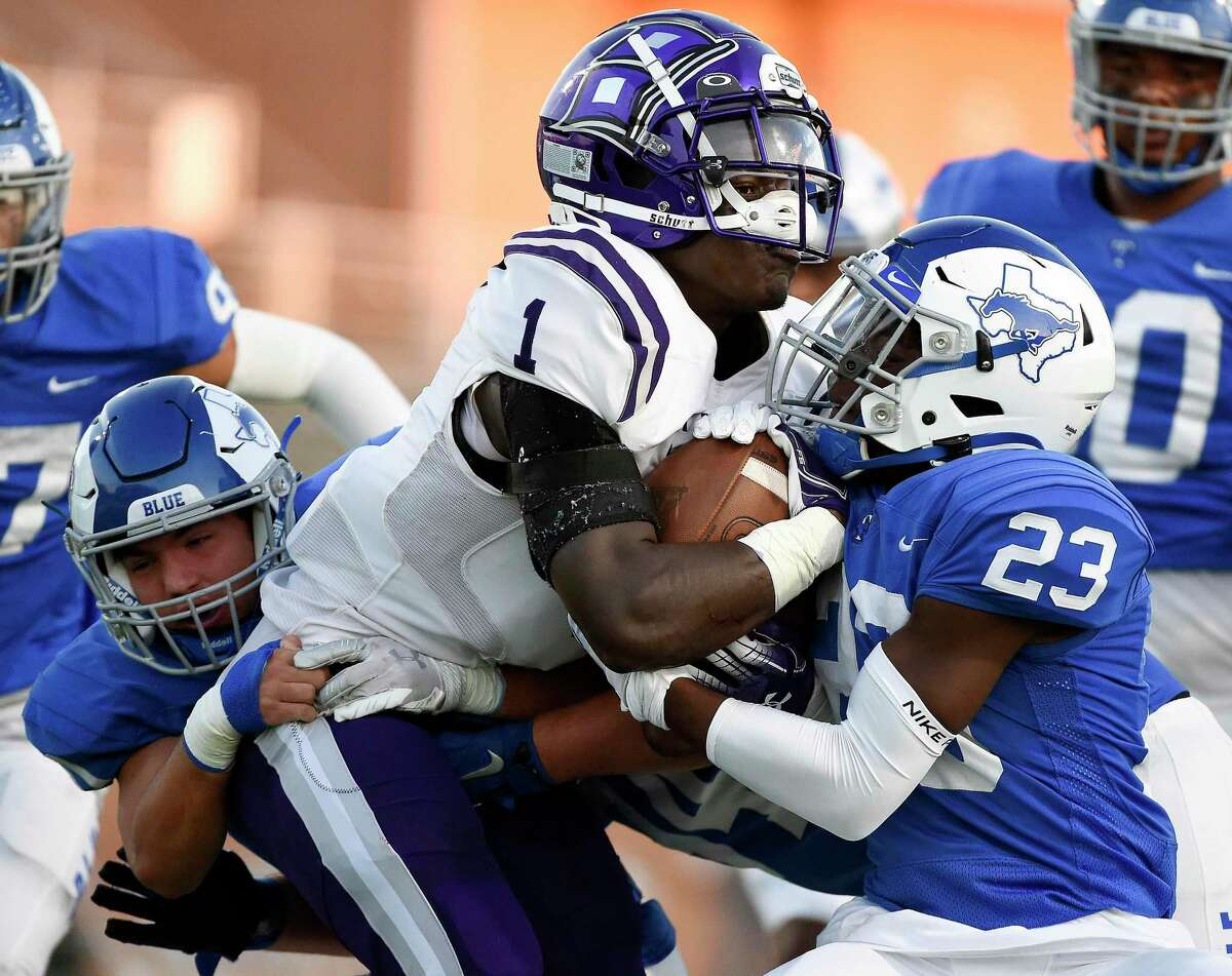 Klein Cain running back Ramir McCray (1) is tackled by Katy Taylor defensive backs Jase Forester, left, and Brandon Wallace (23) during the first half of a high school football game, Friday, Sept. 17, 2021, in Katy.