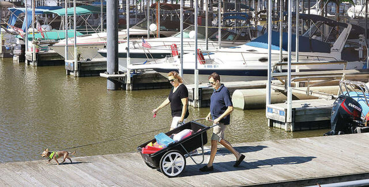 A boater and his dog slowly glide into the refueling dock this week at the Alton Marina.
