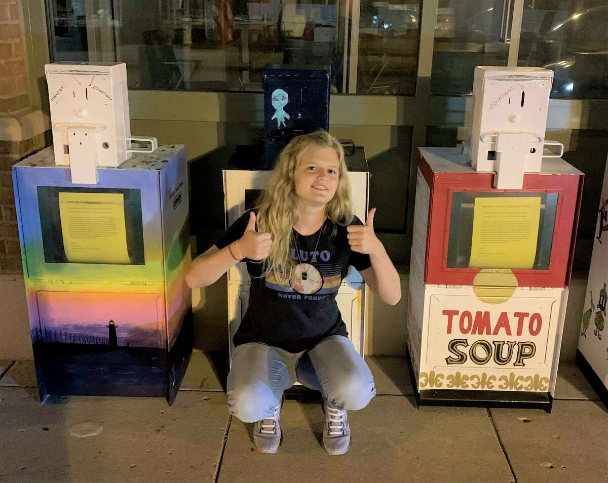 Bay Anderson poses with her two entries for the food pantry design contest held by Manistee County Veterans Affairs. Anderson's entries placed first and second. (Courtesy photo)