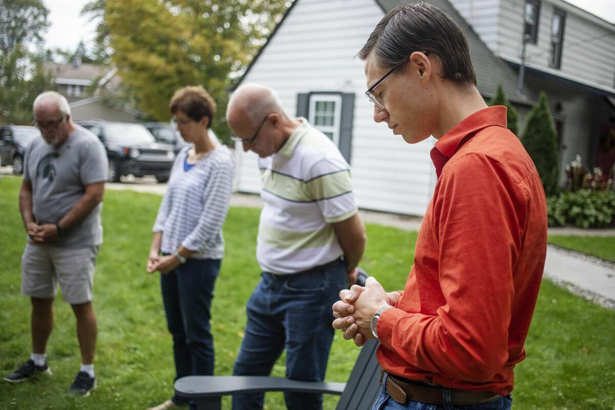 Ethan Head, a case manager for Midland's Open Door, right, voices his prayers during a group prayer on the first day of the organization's annual Prayer Week, Monday, Sept. 20, 2021 at 412 W. Buttles Street in Midland. (Katy Kildee/kkildee@mdn.net)