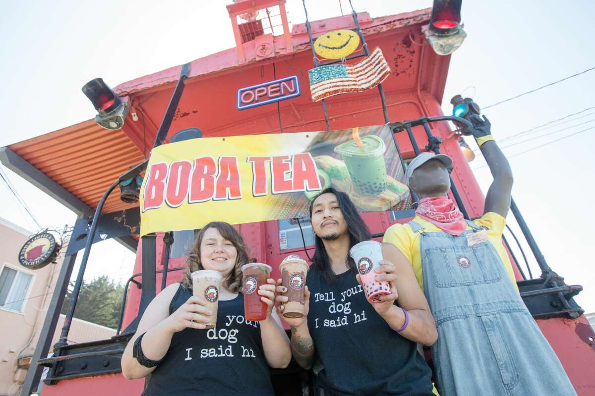 P-Town Coffee and Tea owners Ashlee Shelton, left, and Jeremy-Tristahn Bascara Jr.hold some of their signature boba offerings outside their cafe, located in a train caboose, in Pacifica, Calif.