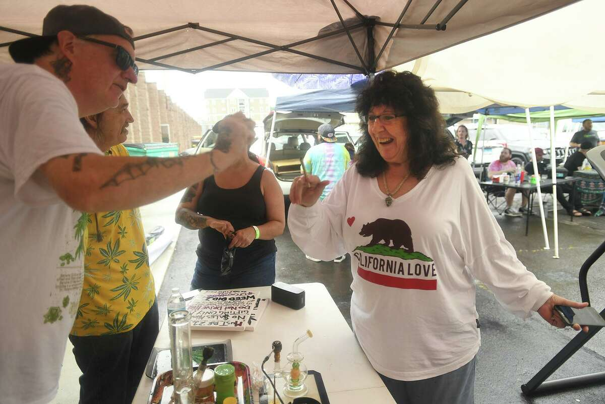 Tim Doherty, left, of Norwalk, hands a free marijuana cigarette to Dale Sheehan, of Wallingford, during the Connecticut Cannawarrior Victory Barbecue in Hamden, Conn. on Thursday, July 01, 2021.