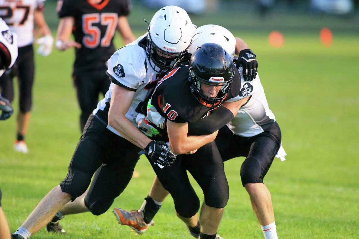 Ubly quarterback Evan Peruski (10) tries to reach toward the goal line as he's tackled by a couple of Harbor Beach defenders.(Eric Young/Huron Daily Tribune)