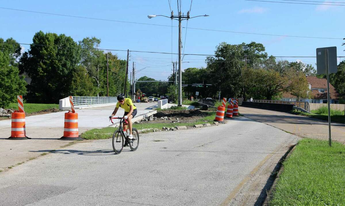 A cyclist pedals past a new bridge that has been constructed over Horsepen Bayou.