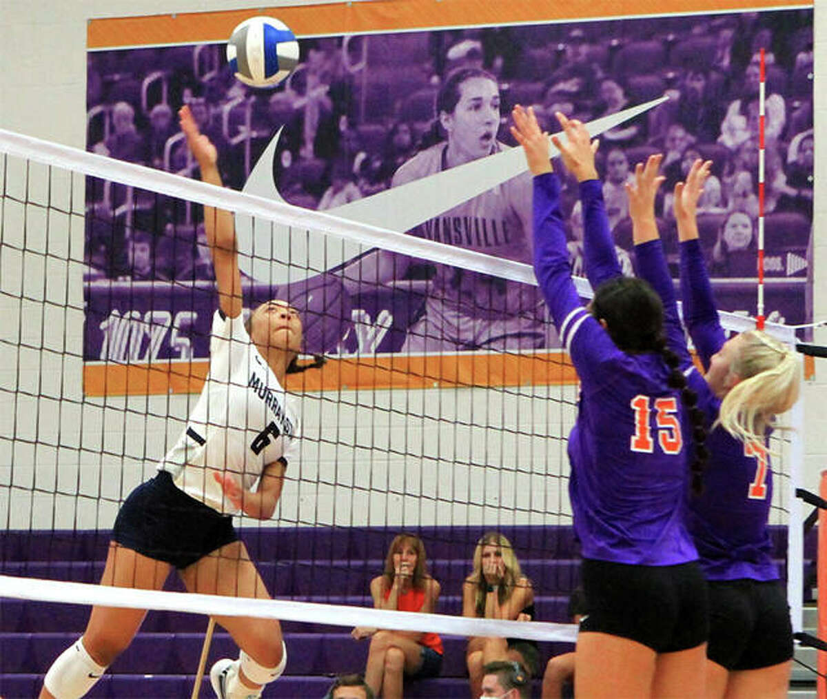 Murray State's Alexa Harris (left), a freshman from Edwardsville, goes above a double block by Evansville for an attack in a match Saturday at Evansville's tournament in Indiana.