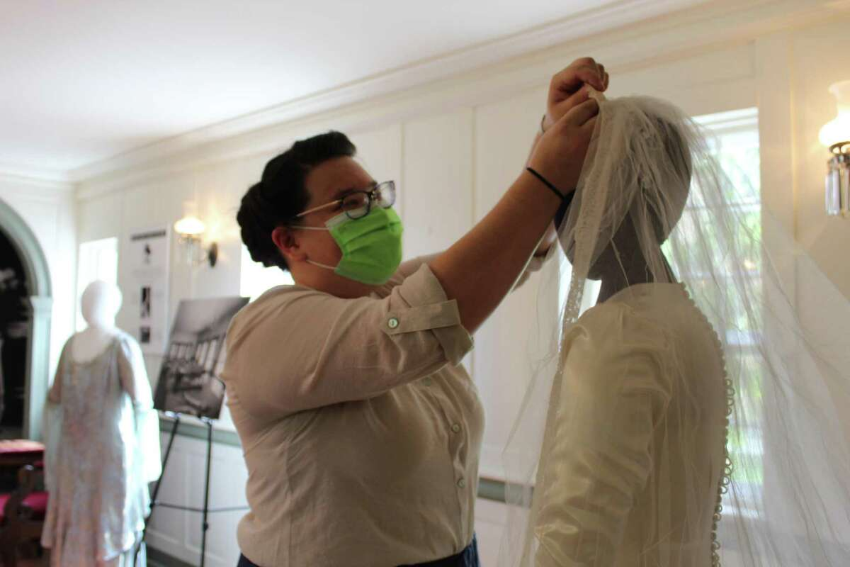 Keeler Tavern Museum's Chief Curator Catherine Prescott adjusts a wedding veil worn by Julia Post Bastedo in 1941. Bastedo was the first bride to ever have her reception in the museum's garden house.