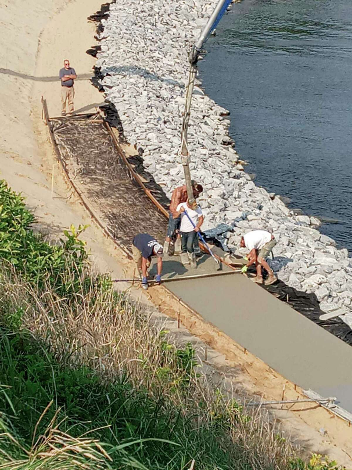 Workers work on the sidewalk of the riverwalk on Cherry and First streets on Friday; 90% of the sidewalk has been poured. The construction is part of ongoing efforts to repair parts of the Riverwalk damaged by erosion. (Courtesy Photo)