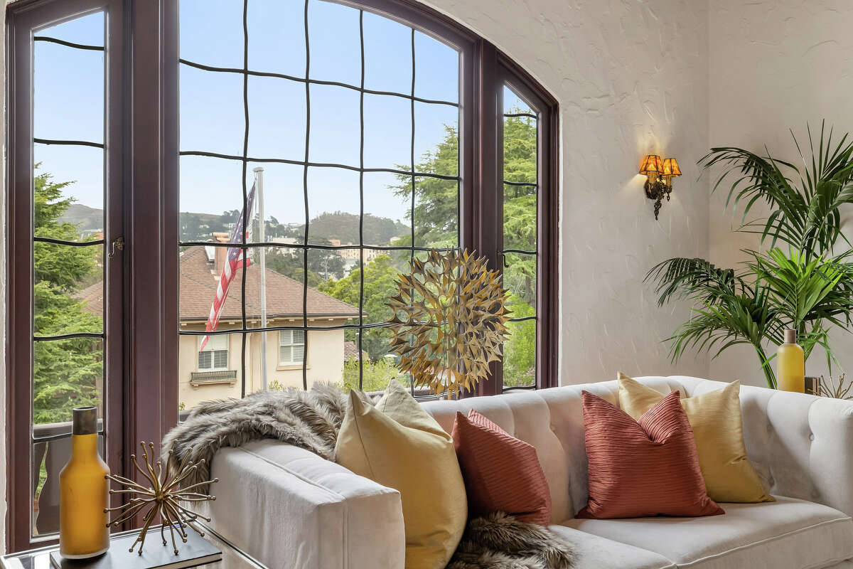 The living room's drama is lightened by this large leaded glass window.