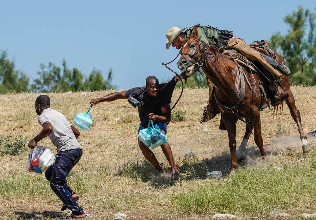 A Texas border patrol agent on horseback tries to stop a Haitian migrant from entering an encampment on the banks of the Rio Grande near the Acuna Del Rio International Bridge in Del Rio, Texas on September 19, 2021.