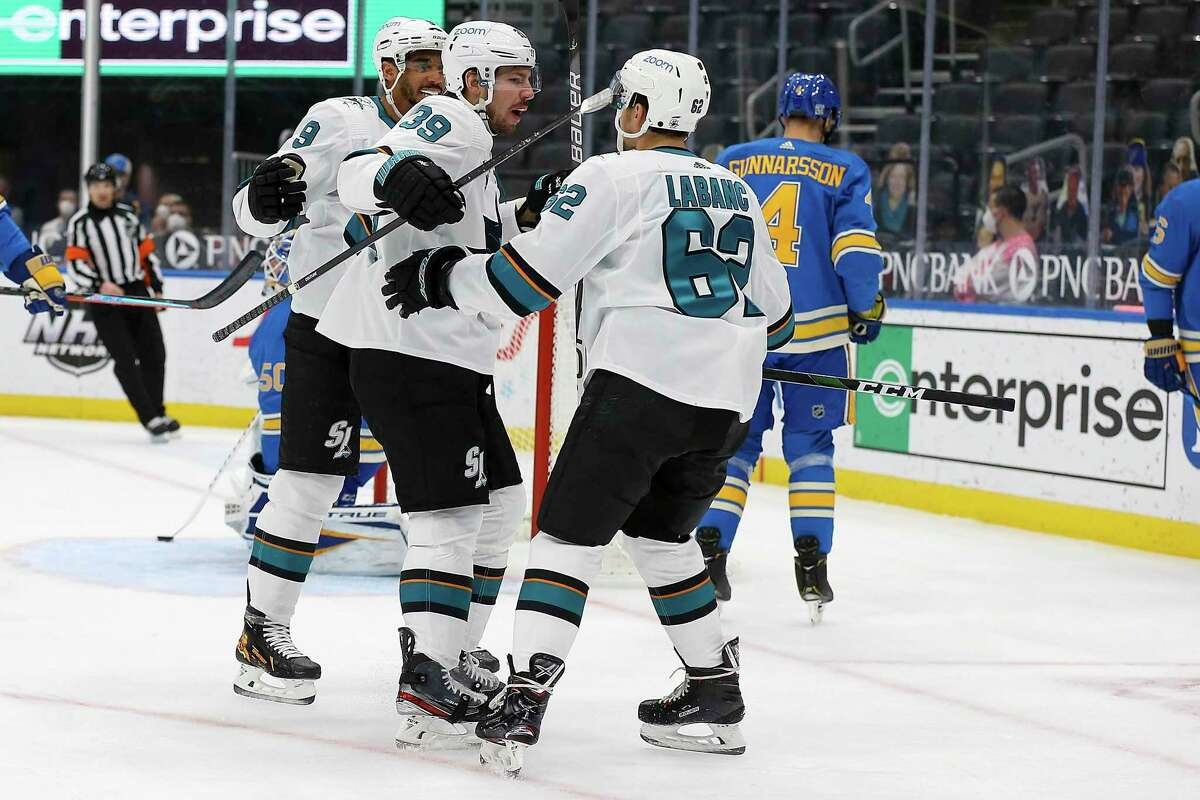 San Jose Sharks' Logan Couture (39), center, is congratulated by teammates Evander Kane, left, and Kevin Labanc, right after scoring a goal during the first period of an NHL hockey game against the St. Louis Blues Saturday Feb. 20, 2021, in St. Louis. (AP Photo/Scott Kane)