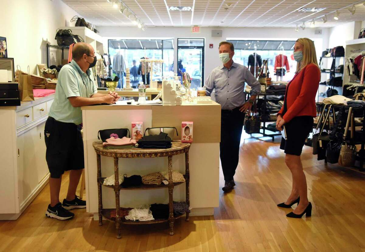 Larry Hoffman, left, husband of the owner of Whim, chats with Connecticut Gov. Ned Lamont and Stamford Democratic mayoral candidate Caroline Simmons at Whim clothing store in Stamford, Conn. Monday, Sept. 20, 2021. Gov. Lamont visited Stamford Monday to talk with small businesses and endorse Caroline Simmons for Mayor of Stamford.
