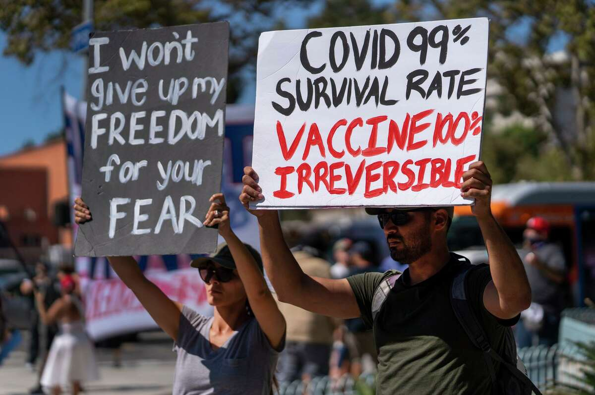 Protesters opposing COVID-19 vaccine mandates hold a rally in front of City Hall in downtown Los Angeles.