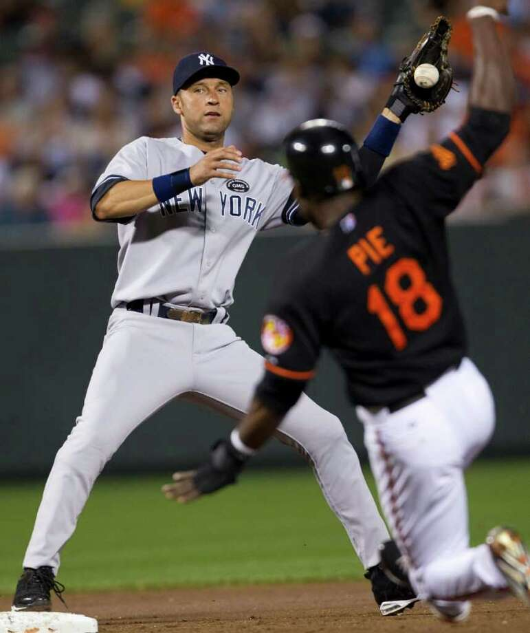 New York Yankees shortstop Derek Jeter forces out Baltimore Orioles' Felix Pie (18) at second base then drop the ball failing to get the runner at first during the second inning of a baseball game, Friday, Sept. 17, 2010, in Baltimore. (AP Photo/Rob Carr) Photo: AP