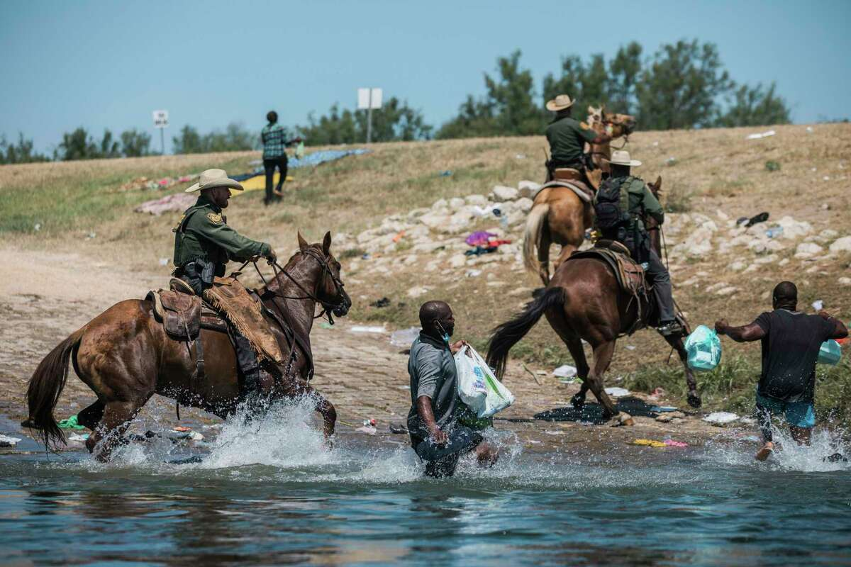 U.S. Customs and Border Protection mounted officers attempt to contain migrants as they cross the Rio Grande from Ciudad Acuña into Del Rio, Texas, Sunday, Sept. 19, 2021. Thousands of Haitian migrants have been arriving to Del Rio, Texas, as authorities attempt to close the border to stop the flow of migrants. (AP Photo/Felix Marquez)