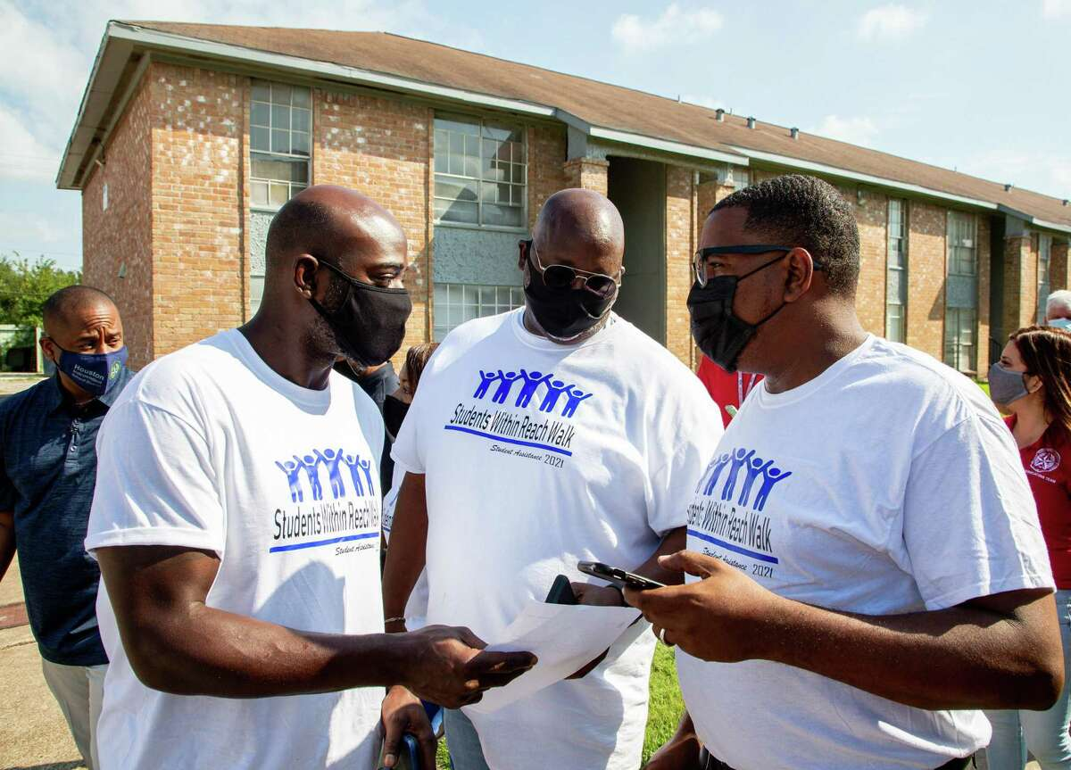 """Superintendent Millard House II, left, along with Houston ISD staff and community volunteers, were knocking on doors to personally encourage students to return to school during the annual """"Students Within Reach Walk"""" on Saturday in Houston."""