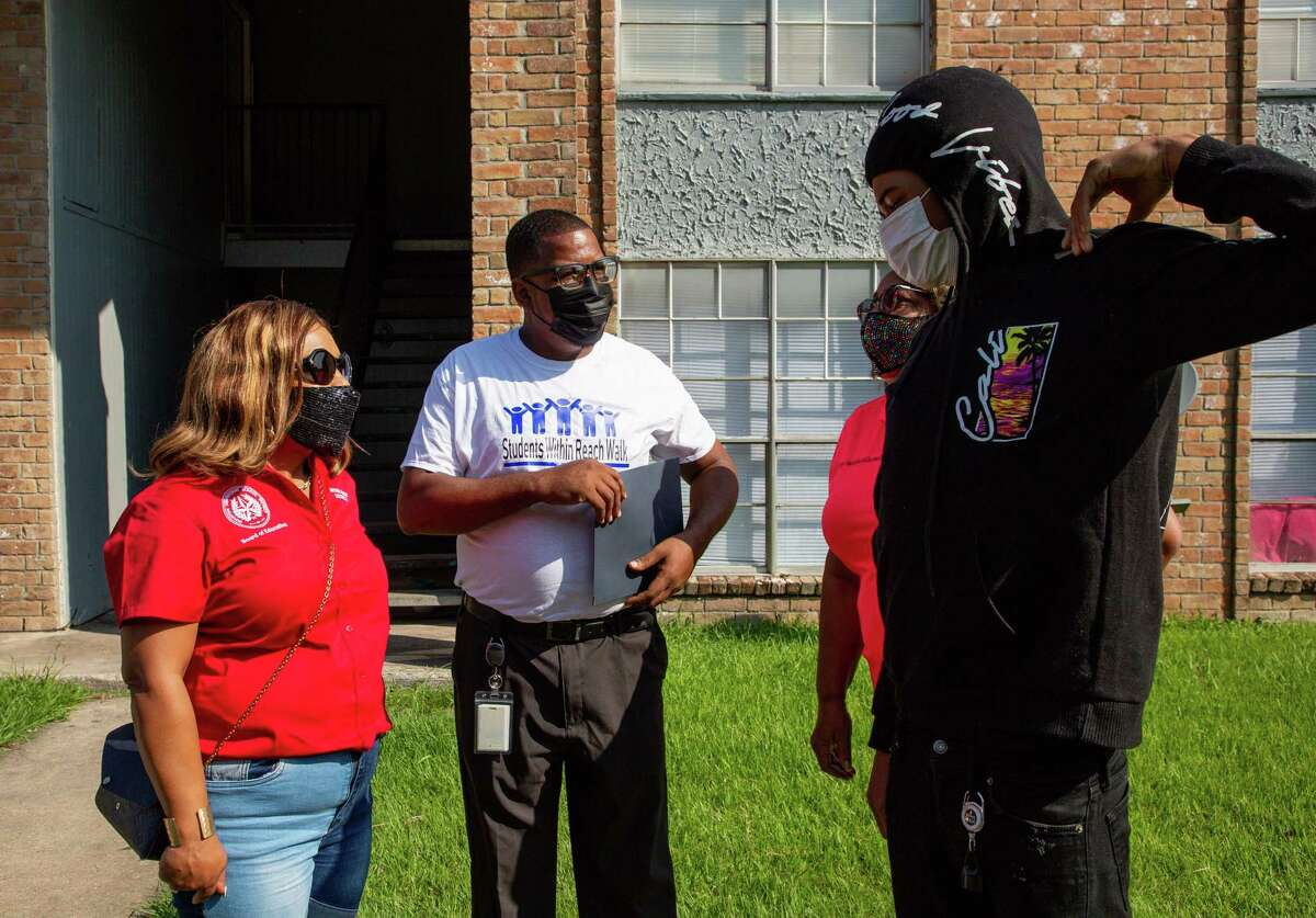 Kashmere High School principal Brandon Dickerson, center, talks with Floyd Young - a student who had stopped attending school - during the annual Students Within Reach Walk on Saturday, Sept. 18, 2021, in Houston.