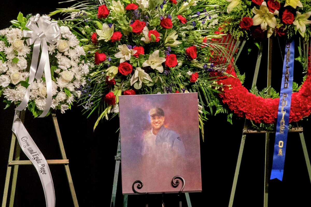 A painting sits near large displays of flower wreaths during a memorial service at Pinole High School in June 2020 for Dave Patrick Underwood, a contract security officer for the Department of Homeland Security who was shot and killed while guarding the Ronald V. Dellums Federal Building in Oakland on May 29, 2020.