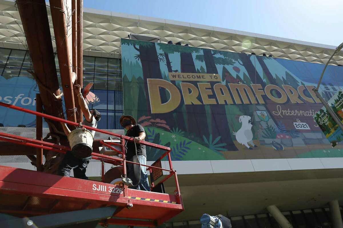 Eksel Perez (left), installer and Robert Schmitt, installer/decorator, work on the set up of Salesforce's Dreamforce 2021 conference as they work on Howard Street in San Francisco.