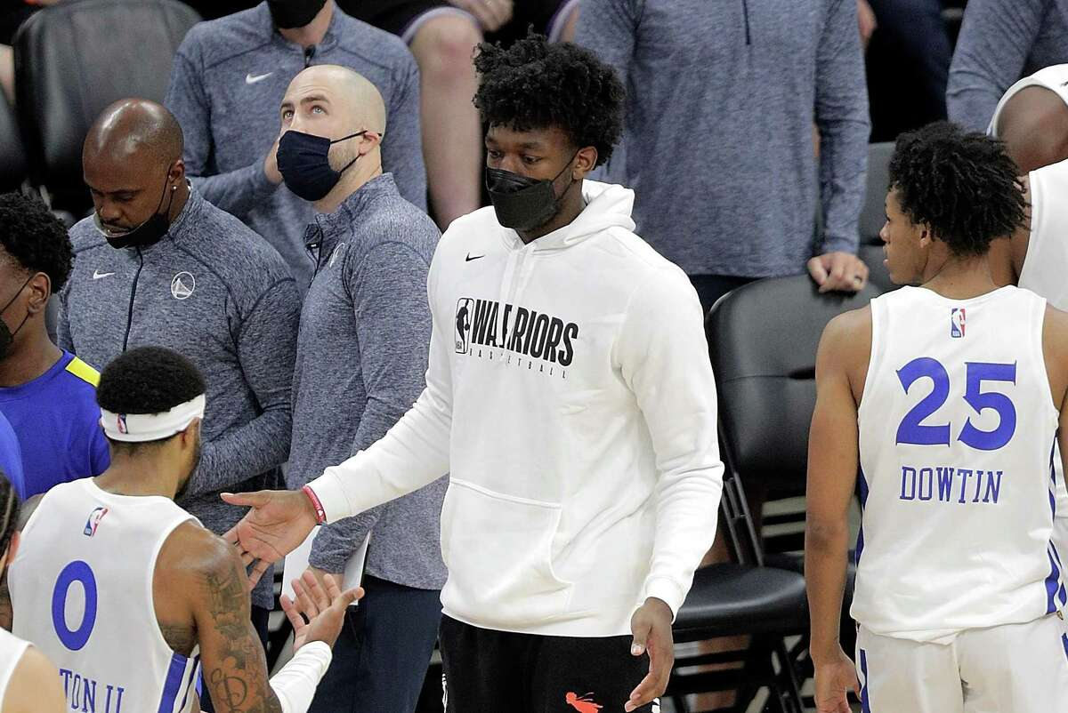 James Wiseman, center, high fives summer league players during a timeout in the second half as the Golden State Warriors summer league played the Miami Heat Summer league in the 2021 California Classic at Golden 1 Center in Sacramento, Calif., on Wednesday, August 4, 2021.