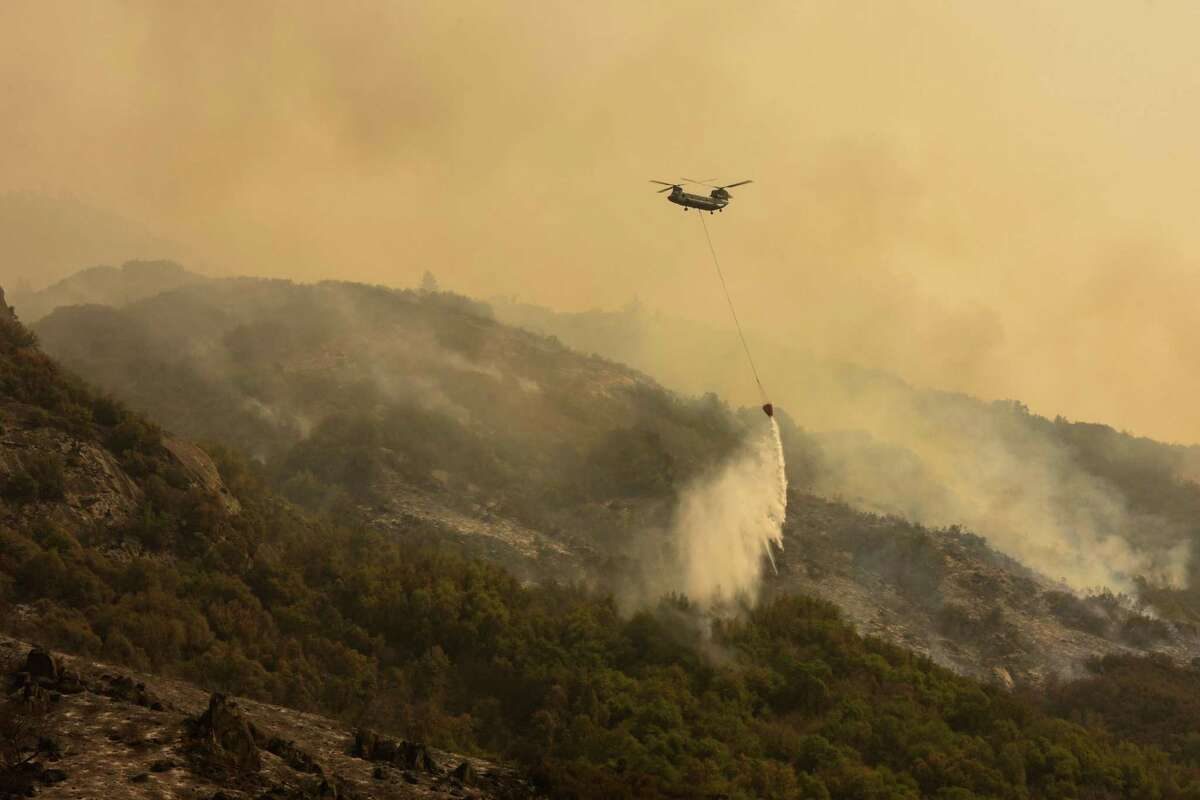 A firefighting helicopter drops water on the KNP Complex fire above Generals Highway in Sequoia National Park. Smoke from wildfires was expected to drift over the Bay Area, casing hazy skies.