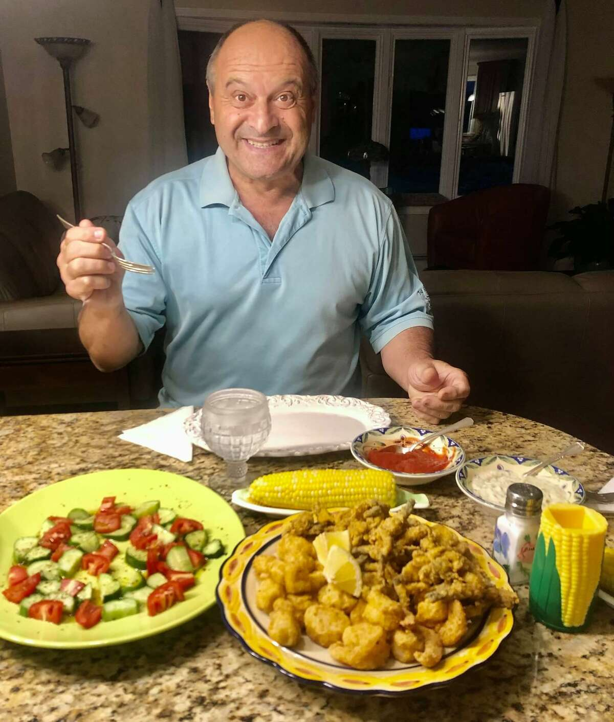 """All Pete Leonetti has to do is smile for the camera in front of his wife Karen's culinary delights and then, of course, indulge. Her Facebook posts of his meals five or so times a week have become a Facebook sensation, with people all over the country wondering, """"How does Pete stay so trim?"""" and """"Why can't my wife cook like that?"""" Here Pete is ready to dig into one of his favorites: a fried seafood platter with homemade tartar sauce, corn on the cob and cucumber and tomato salad."""