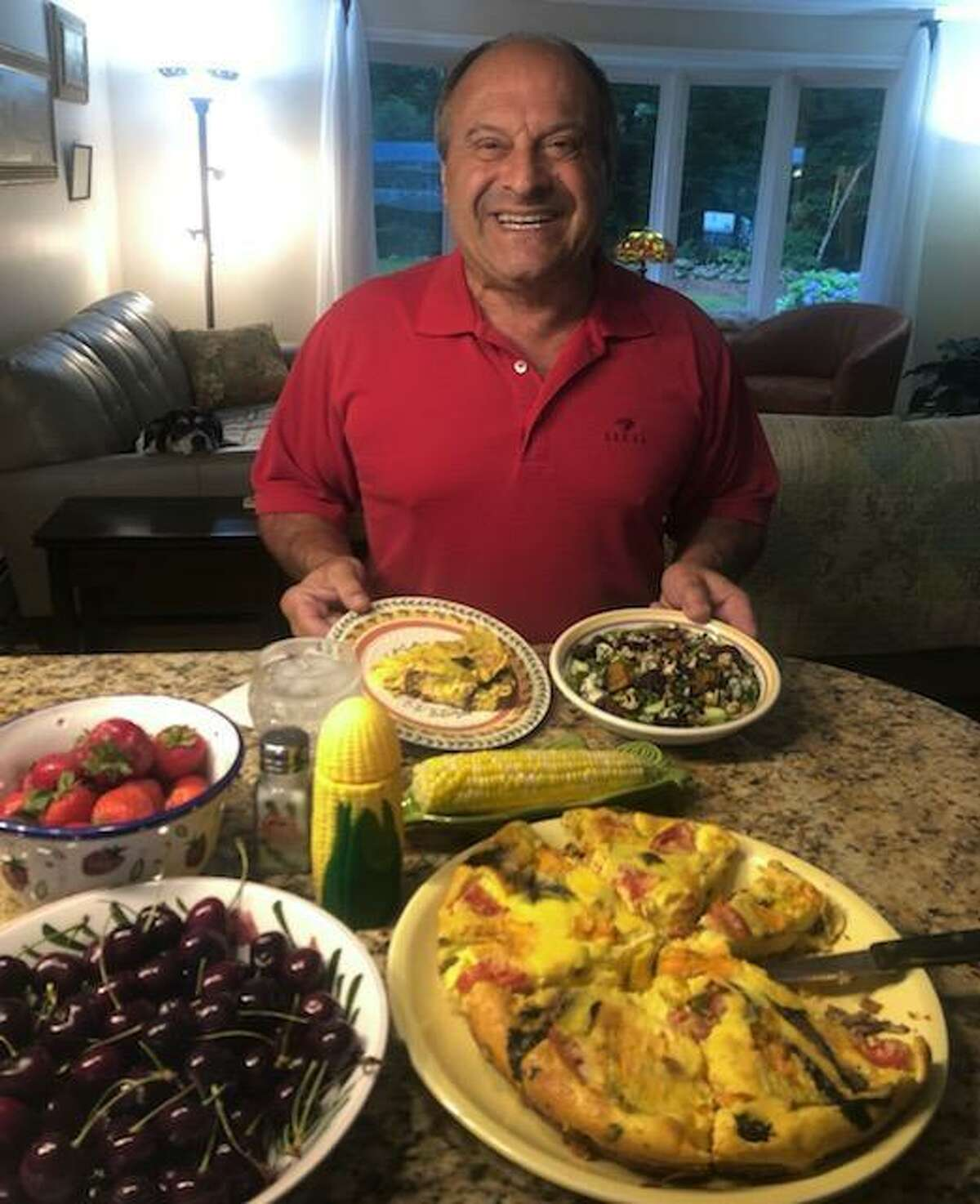 """Pete Leonetti sits before yet another feast prepared by his wife of 39 years, Karen Leonetti. Pete has become a Facebook sensation first through the group """"Wooster Square Cooks,"""" and now through his wife's Facebook group, """"Karen and Pete's Wooster Street Family."""" Hundreds follow Pete and his meals."""