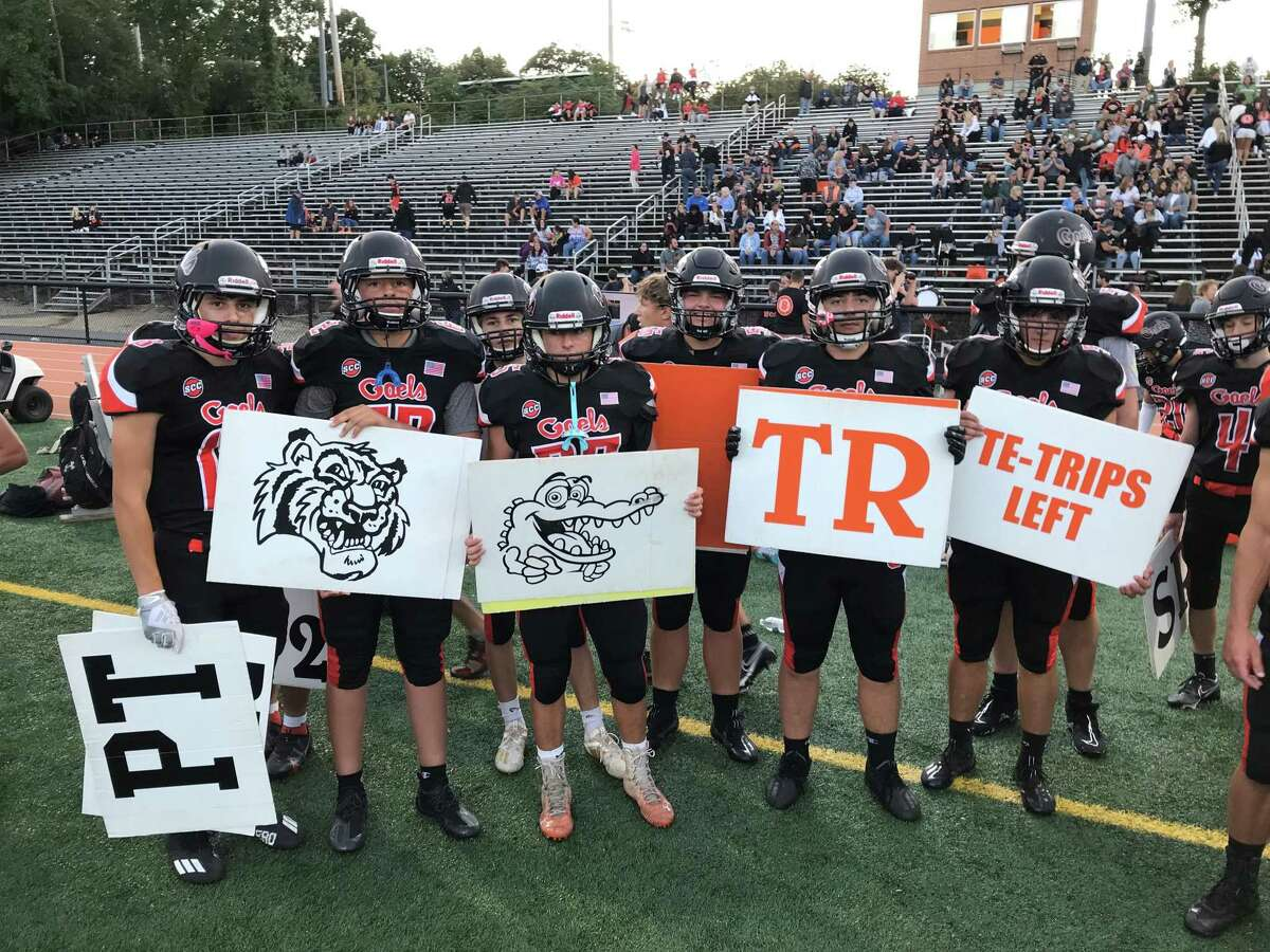 Members of the Shelton football team hold playcards at a recent game.