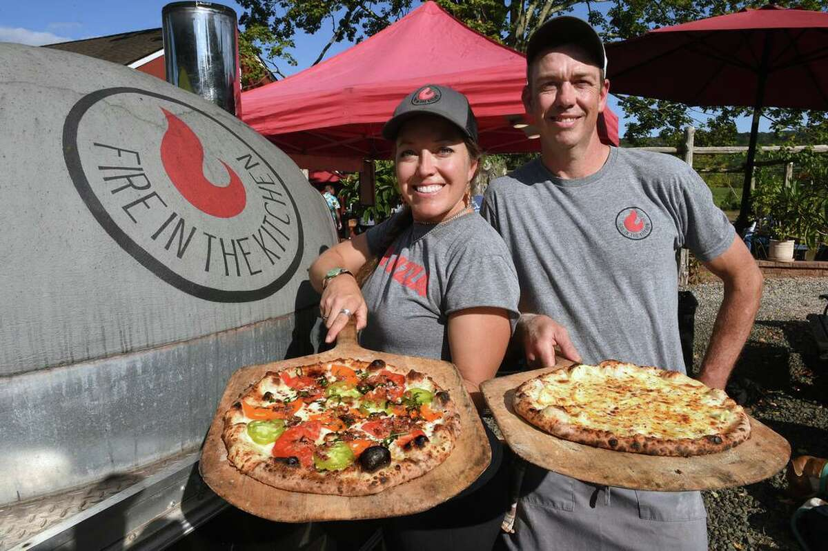 Fire in the Kitchen owners Kristen Griffin and her husband, Matt, holding the specialty pizzas, Hitchhiker and Lemon Boy, respectively, next to their wood-fired pizza oven in front of Rosabianca Vineyards in Northford on Sept. 10.