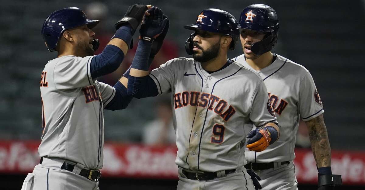 Houston Astros' Marwin Gonzalez, center, celebrates his grand-slam home run with Yuli Gurriel, left, and Carlos Correa during the ninth inning of a baseball game against the Los Angeles Angels Monday, Sept. 20, 2021, in Anaheim, Calif. (AP Photo/Marcio Jose Sanchez)