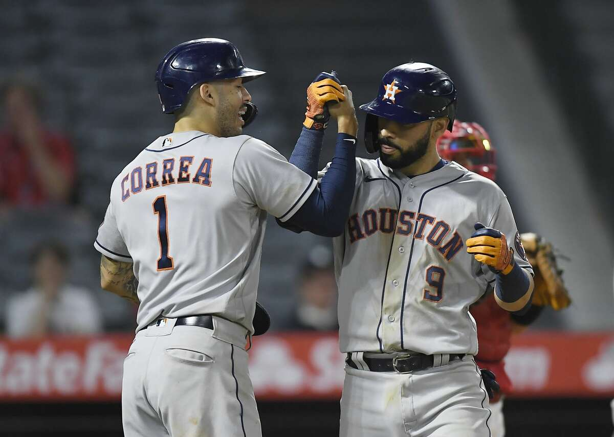 ANAHEIM, CA - SEPTEMBER 20: Marwin Gonzalez #9 of the Houston Astros is congratulated by Carlos Correa #1 after hitting a grand slam home run against relief pitcher Jose Marte #68 of the Los Angeles Angels during the ninth inning at Angel Stadium of Anaheim on September 20, 2021 in Anaheim, California. (Photo by Kevork Djansezian/Getty Images)