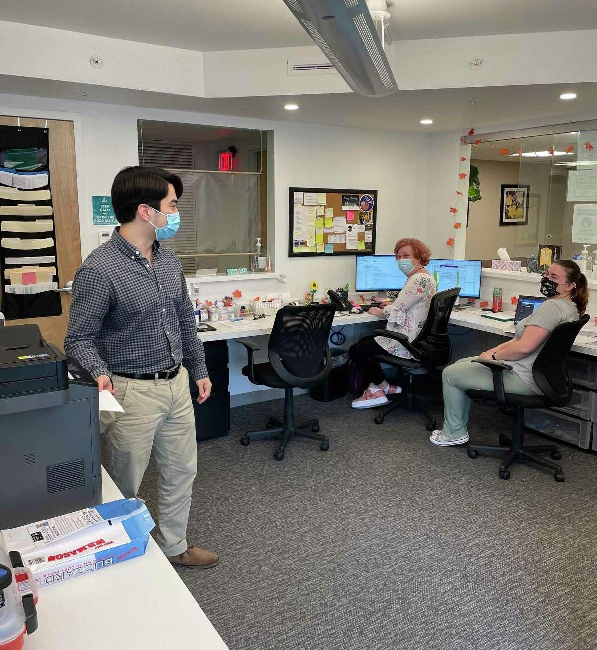 At Autism Behavioral Health in Danbury, Nicholas Rosenhaus, HR specialist, talks with Linda Solimine, administrative assistant, and Aleena Sirota, a registered behavior technician.