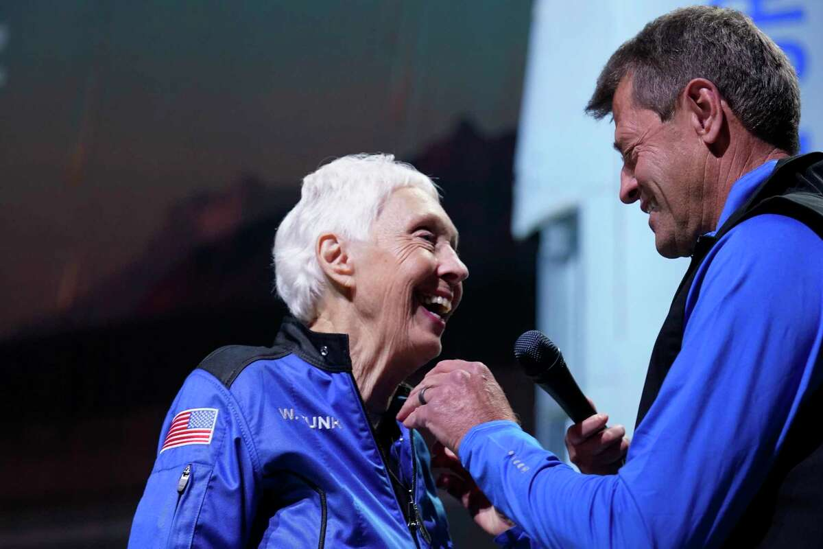 Wally Funk is awarded the Blue Origin-made astronaut pin by former NASA astronaut, Jeff Ashby, right, who is now based with Blue Origin, during a New Shepard post launch briefing at the spaceport near Van Horn, Texas, July 20, 2021.