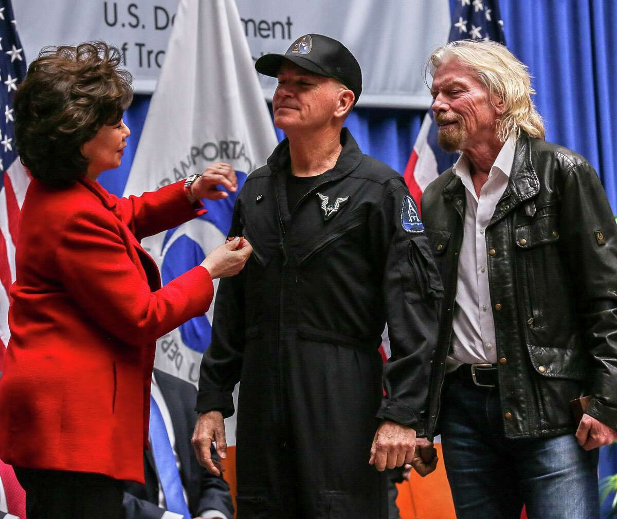 CJ Sturckow, left, receives wings from the FAA's Commercial Space Astronaut Wings program.  Sturckow received these wings because he was a pilot on Virgin Galactic's SpaceShipTwo and flew it over 50 miles above the Earth's surface.  To her right is Virgin Galactic founder Richard Branson.