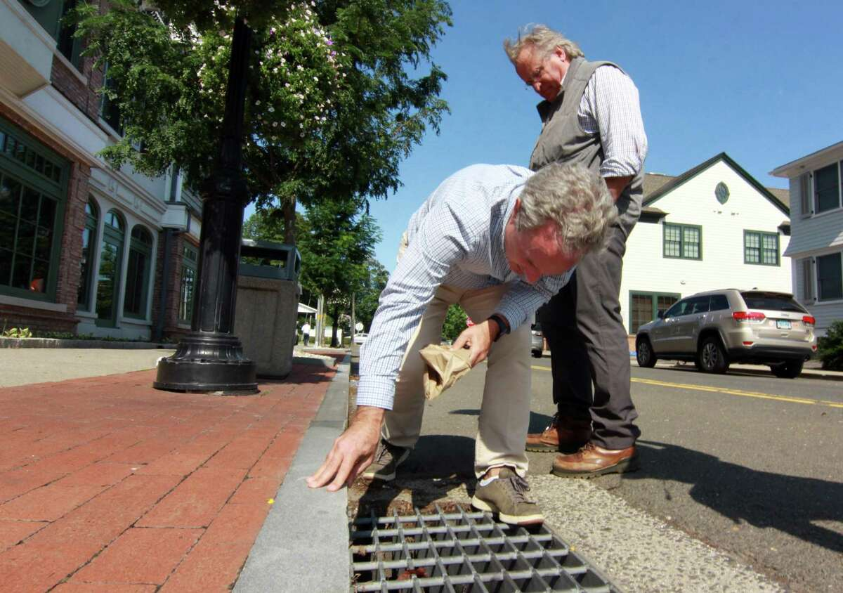 Local business owners Al Tibbetts and David Genovese, standing in back, try to get a look at storm drains that backed up during a tour of businesses damaged by flooding from Hurricane Ida by Governor Ned Lamont and First Selectman Jayme Stevenson in Darien, Conn., on Friday Sentember 10, 2021.
