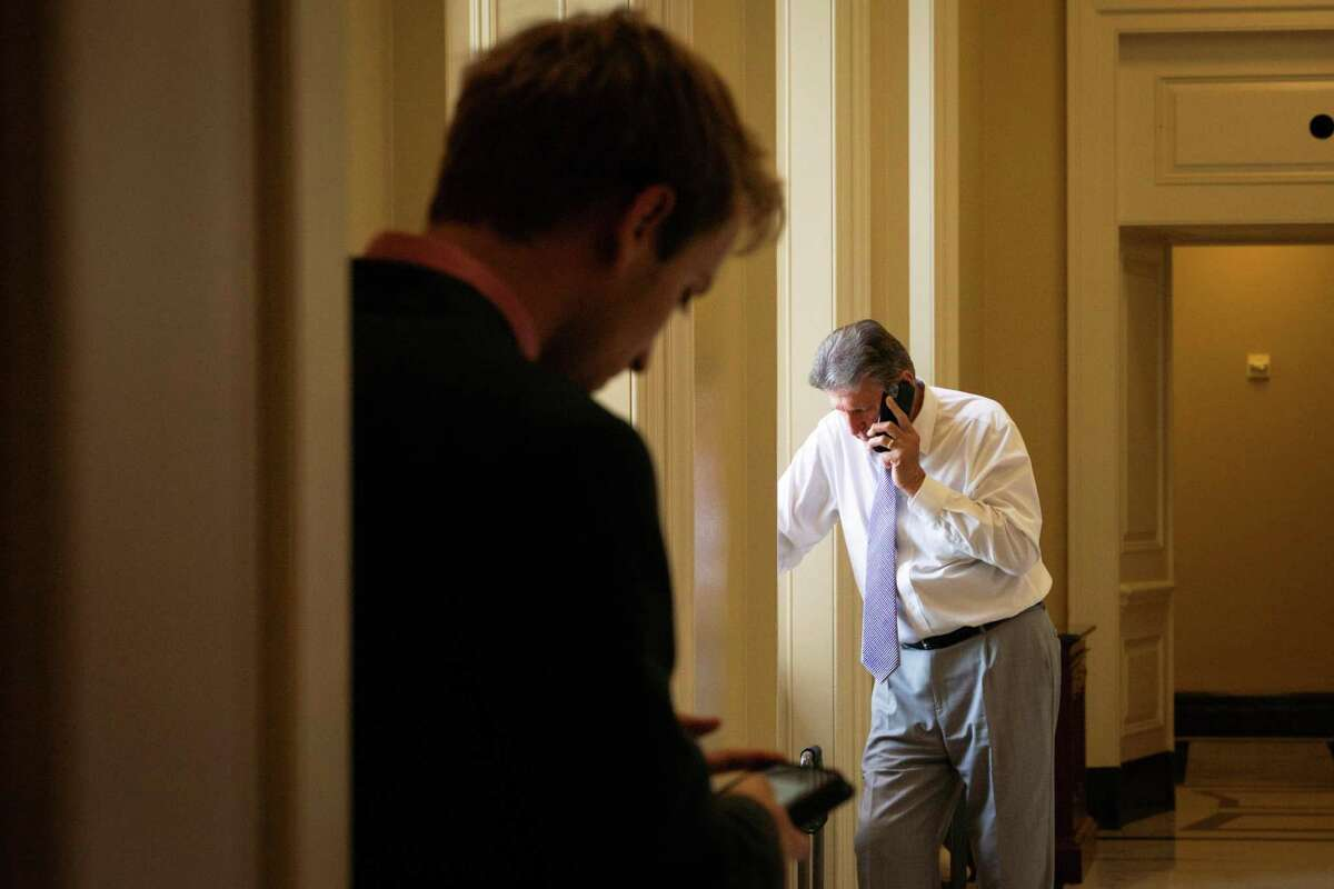 FILE ?' Sen, Joe Manchin (D-W.Va.) takes a phone call at the Capitol in Washington on July 13, 2021. Manchin represents a state that is second in coal and seventh in natural gas production, and personally profits from stock he owns in his family?•s coal brokerage. (Sarahbeth Maney/The New York Times)