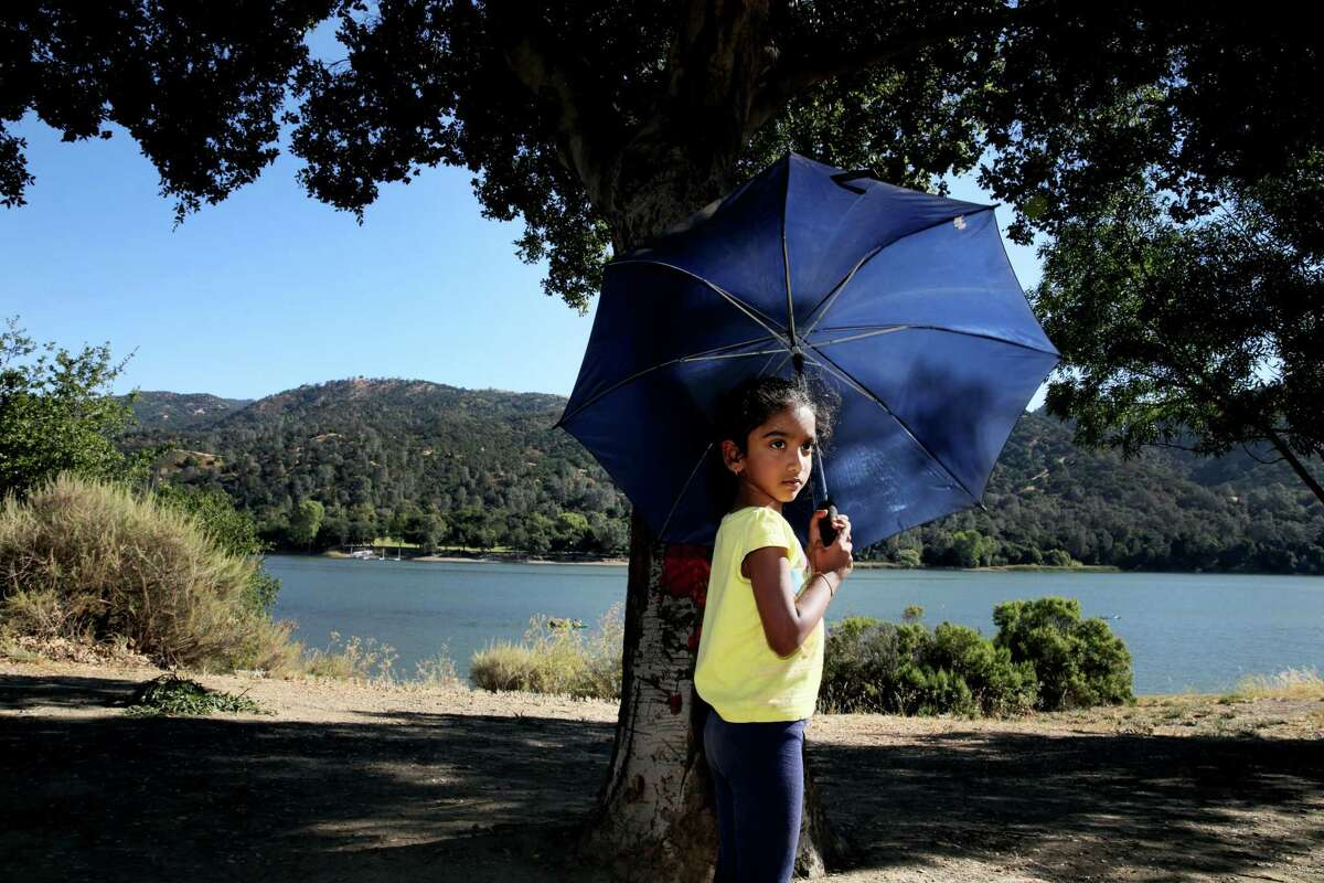 Saindhavi Satheesh, 4, keeps herself cool in the shade while she plays at Del Valle Regional Park in Livermore, Calif. Warm temperatures were in the forecast across the Bay Area on the last day of summer.