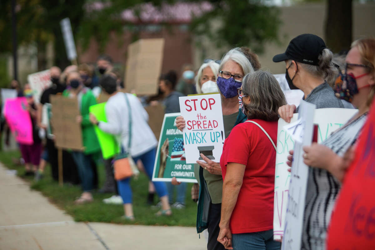 Protesters gather outside of Central Auditorium before a meeting of the Midland Public Schools Board of Education Monday, Sept. 20, 2021 in Midland. The meeting included a presentation from physicians from MidMichigan Health, followed by a public comment session during which many debated about masking in schools. (Katy Kildee/kkildee@mdn.net)