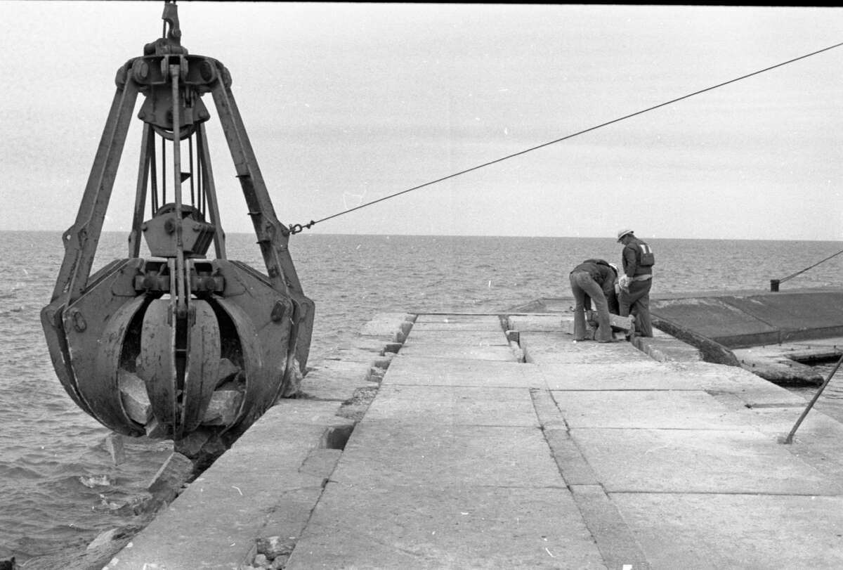 A crew of workers from the U.S. Army Corps of Engineers has been busy stabilizing the First Street Beach pier with large rocks or ballast and will be here another few days, depending upon the weather. Shown above are workers Larry Voight, Pat Kelliher and Elmer Burr. The photo was published in the News Advocate on Sept. 24, 1981. (Manistee County Historical Museum photo)