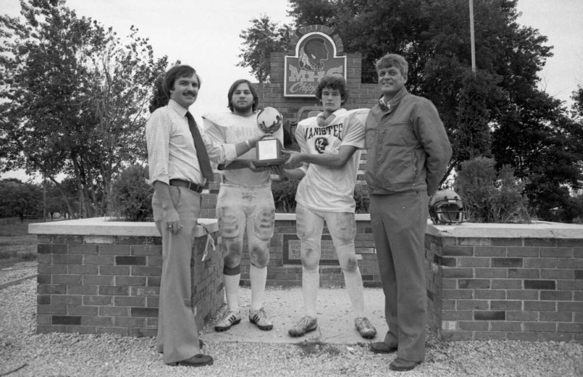 Their fourth consecutive victory over Ludington, a 22-0 shutout registered a week ago, gives the Chippewa football team possession of theManistee High School Dad's Club traveling trophy for one more year. (From left) Mike Welsh, of the Dad's Club; David Landis, Jim Jordan and Coach Duane Wagberg. The photo was published in the News Advocate on Sept. 25, 1981. (Manistee County Historical Museum photo)