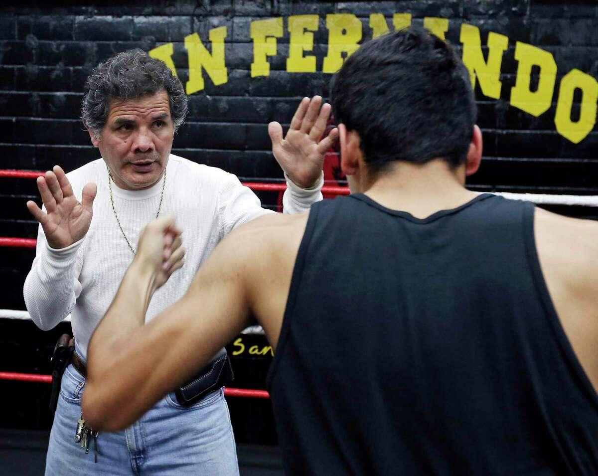 Former pro boxer Mike Ayala, left, works with Golden Gloves boxer Jimmy Martinez on Friday Feb. 19, 2016 at San Fernando Gym.