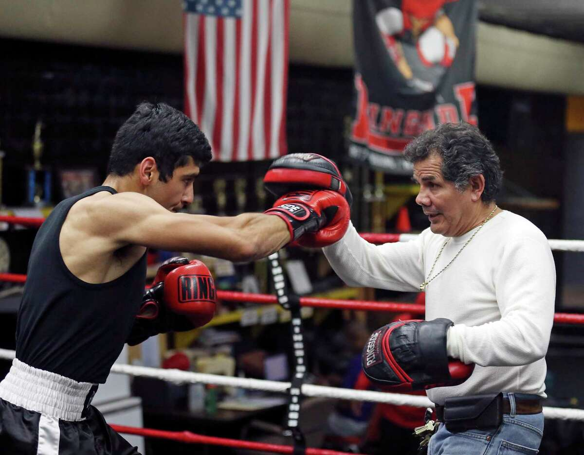 Former pro boxer Mike Ayala, right, works with Golden Gloves boxer Jimmy Martinez on Friday Feb. 19, 2016 at San Fernando Gym.