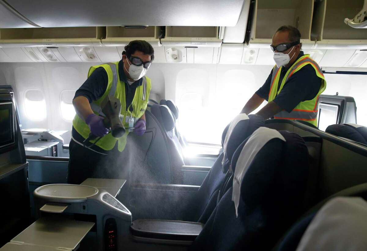 A ground crew sanitizes a United airliner at SFO before it departs for Hawaii in 2020. Tuesday, San Francisco Mayor London Breed announced that everyone who works at SFO must be vaccinated.