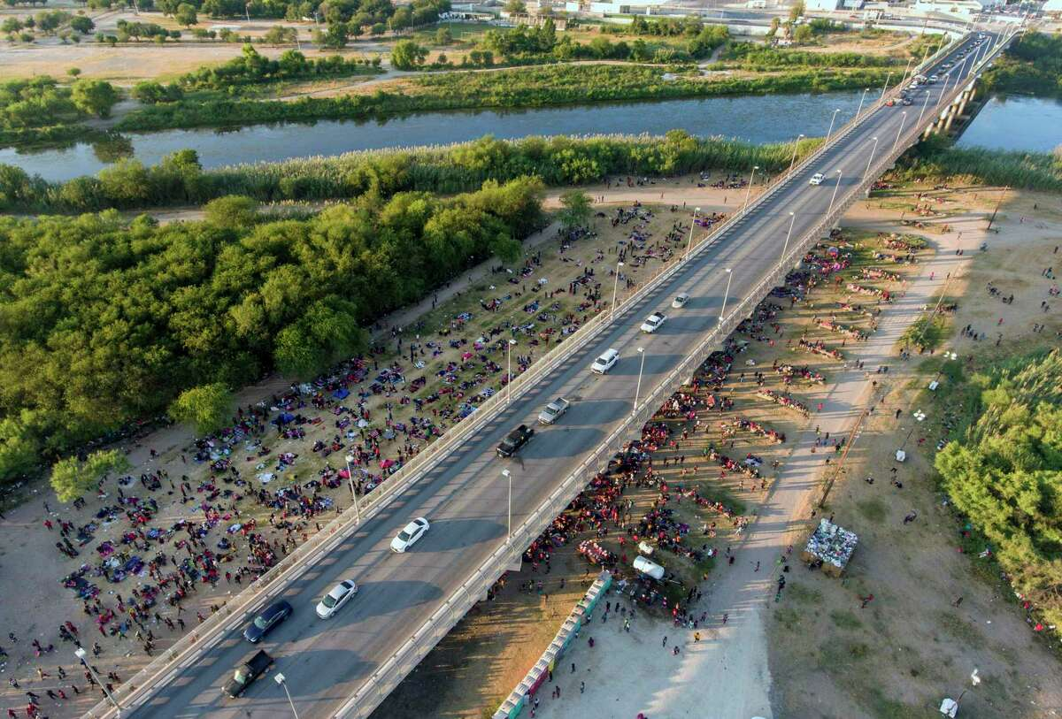 Migrants wait Thursday, Sept. 16, 2021, under and around the international bridge between Del Rio and Ciudad Acuna, Merxico to be processed by immigration officials.