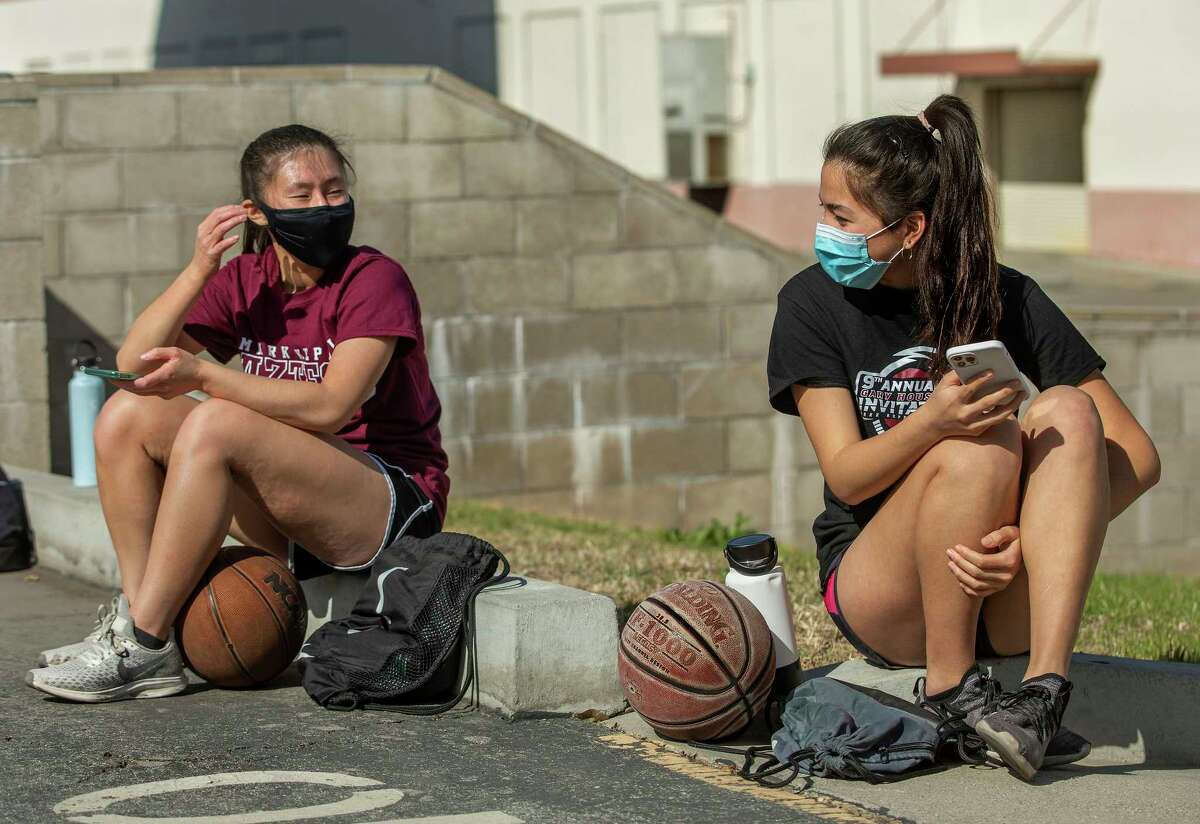 Kendall Tam, left, a senior at Mark Keppel High School and captain of the girls varsity basketball team, talks with Emily Liu, a junior, before the start of a March 26, 2021 practice session at the school in Monterey Park, California.