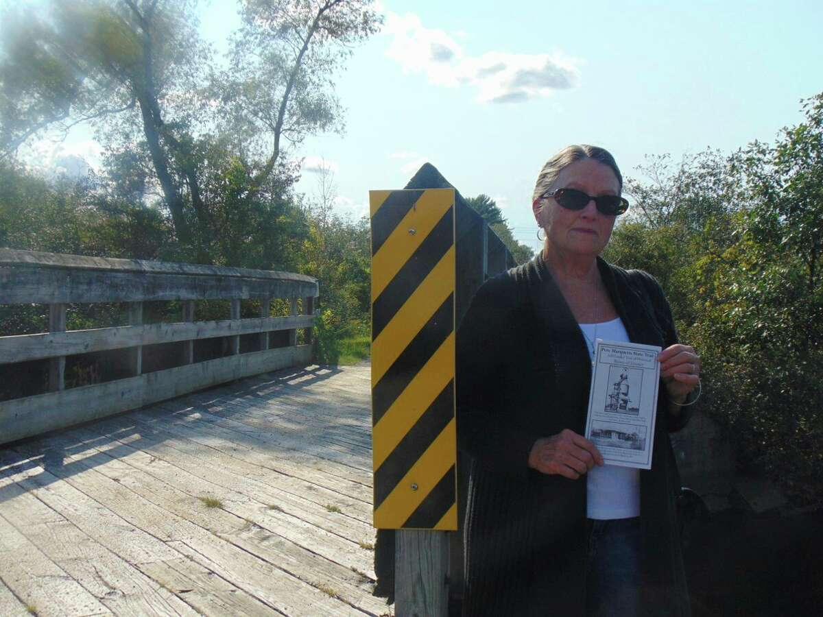 Pam Simmons, promoter for the Pere Marquette State Trail, created the brochure to enhance the trail experience for its users. Pictured: Pam is holding a copy of the brochure at the historical railroad bridge crossing the Baldwin River along the trail. (Star photo/Shanna Avery)